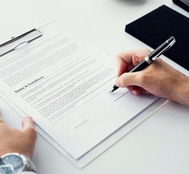 Primer plano de la mano que firma el espacio de trabajo de papel Foto gratis