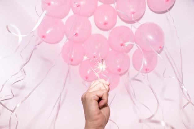 Primer plano de la mano que sostiene una bengala encendida bajo el techo decorativo con globos rosados Foto gratis
