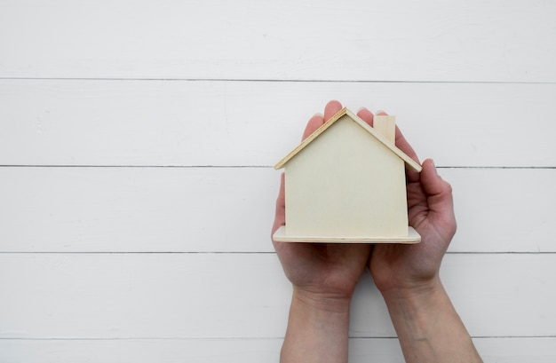 Primer plano de la mano que sostiene el modelo de casa de madera en miniatura contra el fondo blanco de madera Foto gratis