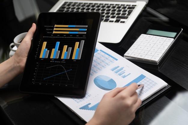 Primer plano de la mano que sostiene la tableta y el lápiz en la tabla Foto Premium