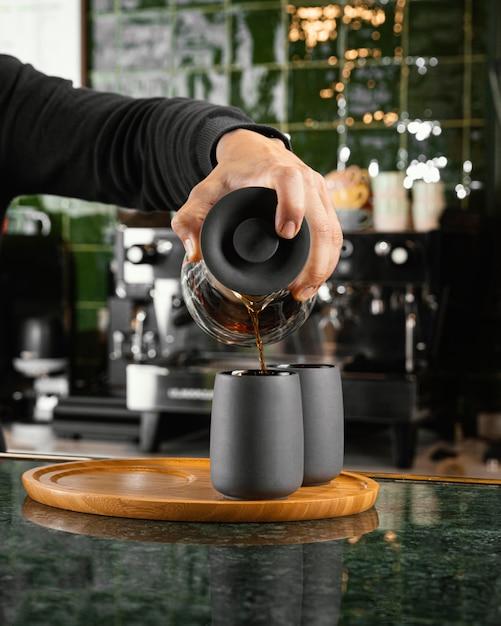 Primer plano mano vertiendo café en taza Foto gratis