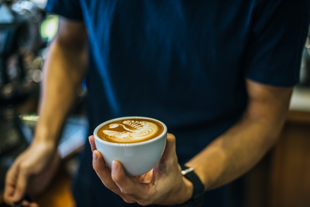 Primer plano de manos barista hacer café con leche arte pintura Foto gratis