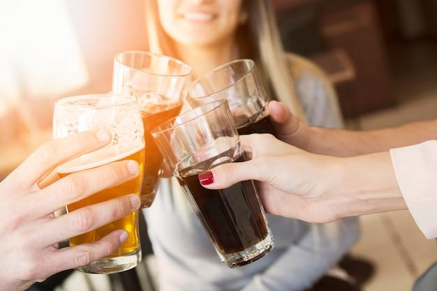 Primer plano de manos brindando vasos de bebidas Foto gratis