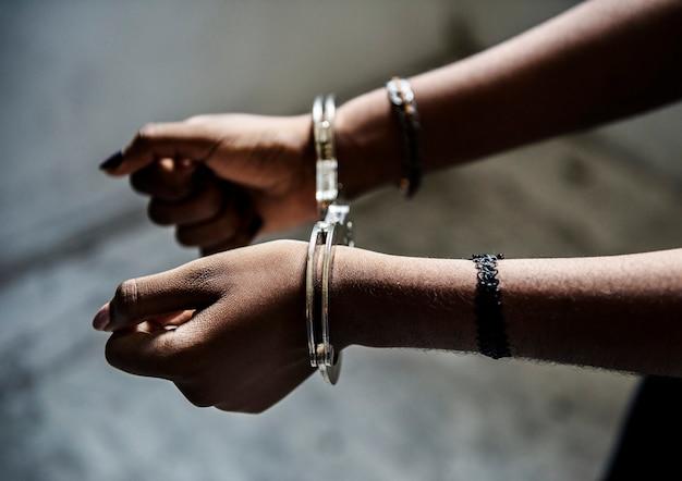 Primer plano de manos detenidas con esposas Foto Premium