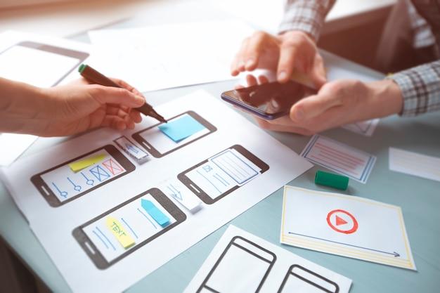 Primer plano de las manos de un diseñador web que desarrolla aplicaciones para la interfaz de usuario de teléfonos móviles. Foto Premium