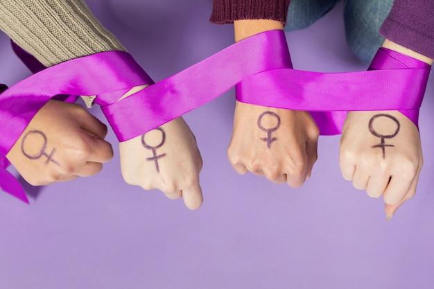 Primer plano de las manos de las mujeres con el símbolo del feminismo Foto gratis