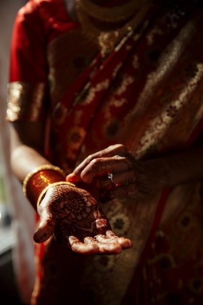 Primer plano de las manos de la novia hindú cubiertas con tatuajes de henna Foto gratis