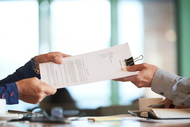 Primer plano de manos pasando el contrato al empresario irreconocible Foto gratis