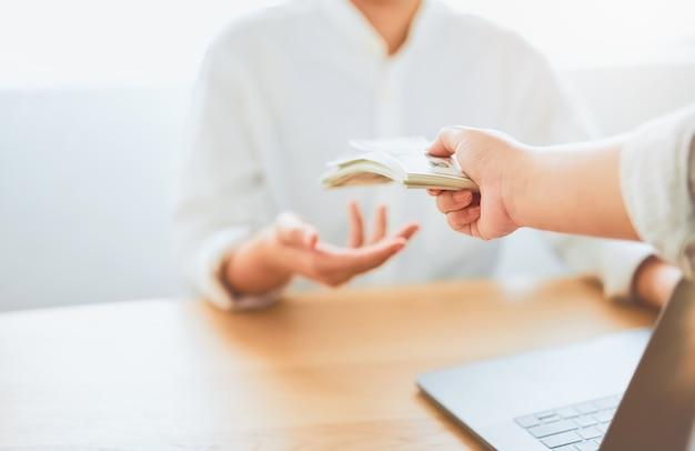 Primer plano de las manos que dan una remuneración en dólares del trabajo Foto Premium