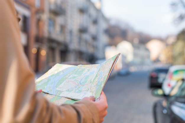 Primer plano del mapa de la tenencia del viajero masculino en la mano que se coloca en la calle de la ciudad Foto gratis