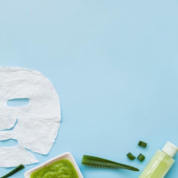 Primer plano de la mascarilla aloevera; botella de spray y hoja sobre fondo azul Foto gratis