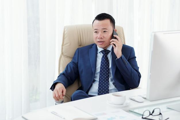 Primer plano medio de empresario asiático haciendo una llamada telefónica sentado en su escritorio de oficina Foto gratis