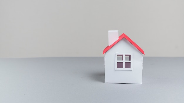 Primer plano del modelo de casa de papel pequeño en superficie gris Foto gratis