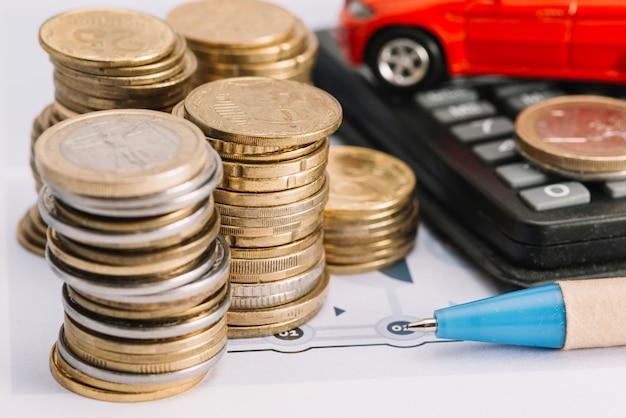 Primer plano de monedas apiladas; bolígrafo y calculadora Foto gratis