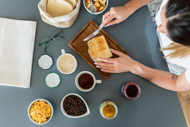 Primer plano de mujer aplicando mermelada en pan sobre el escritorio Foto gratis