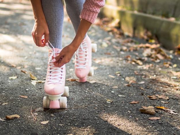 Primer plano de mujer atar cordones de los zapatos en patines con espacio de copia Foto gratis