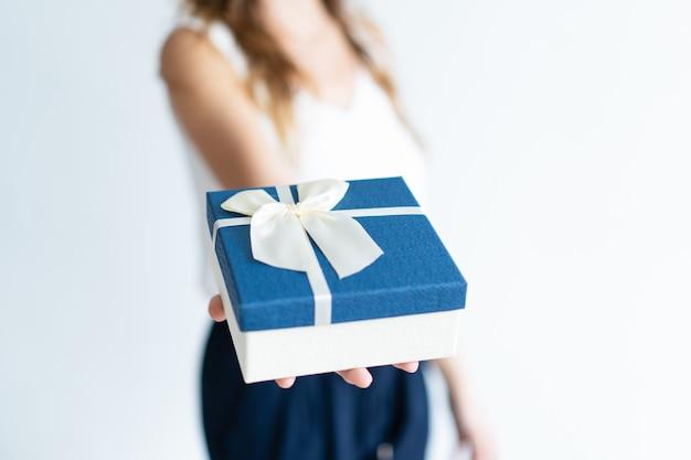 Primer plano de mujer con caja de regalo en la palma Foto gratis