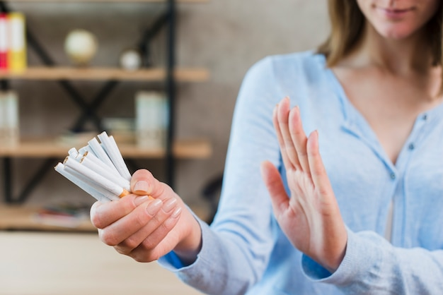Primer plano de mujer diciendo que no sostiene manojo de cigarrillos en la mano Foto gratis