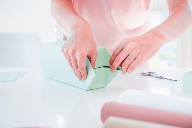Primer plano de una mujer envolviendo la caja de regalo en mesa blanca Foto gratis