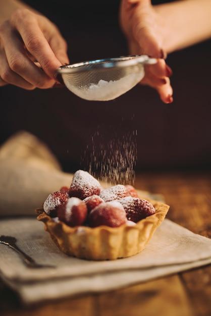 Primer plano de mujer espolvoreando el polvo de azúcar en tarta de fresa Foto gratis