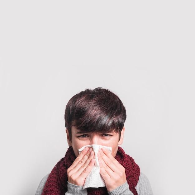 Primer plano de mujer estornudando con tejido sobre fondo blanco Foto gratis