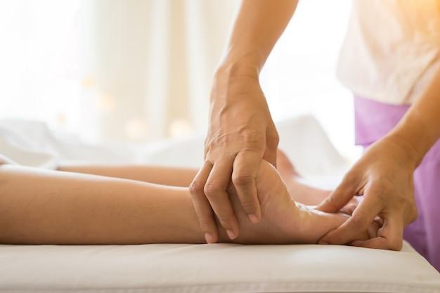 Primer plano de mujer haciendo masaje de pies en el spa. Foto gratis