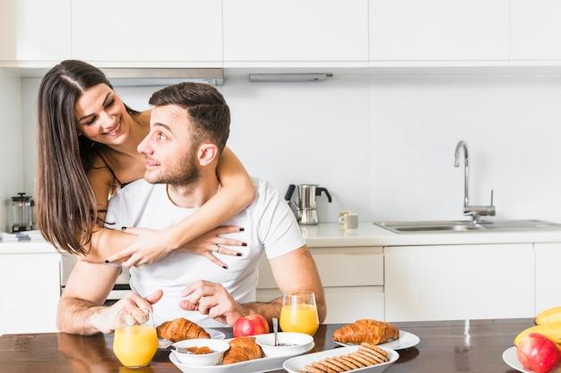 Primer plano de mujer joven abrazando a su novio desayunando Foto gratis