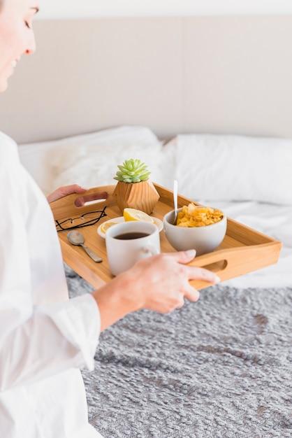 Primer plano de mujer joven con desayuno por la mañana en la bandeja de madera Foto gratis