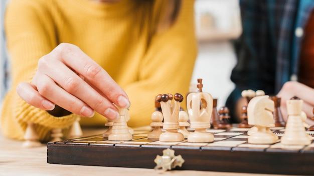 Primer plano de mujer joven jugando el juego de mesa de ajedrez Foto gratis