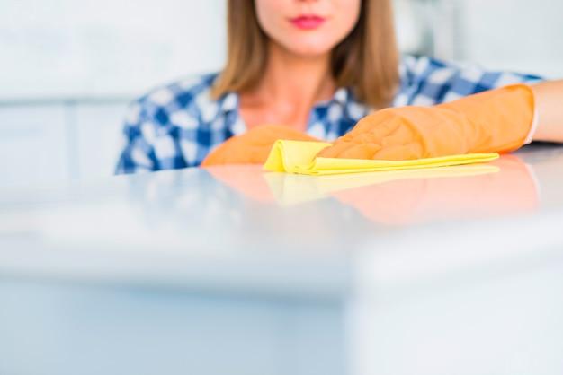 Primer plano de mujer joven limpiando la superficie blanca con plumero amarillo Foto gratis