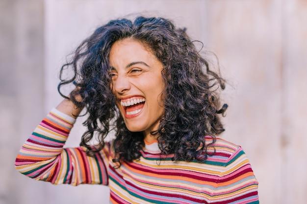 Primer plano de mujer joven sonriente con la mano en la cabeza Foto Premium