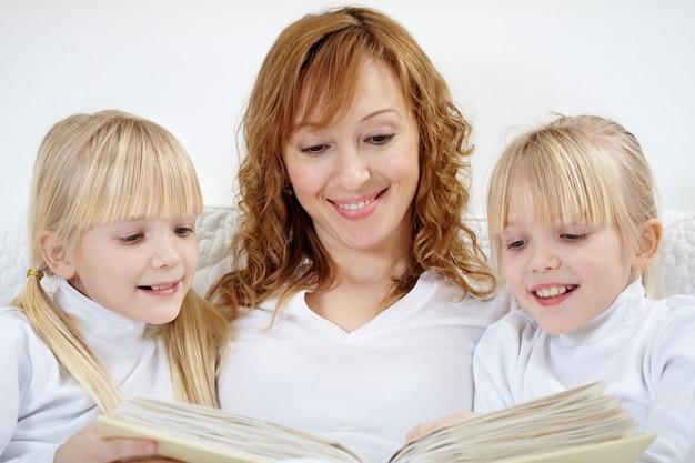 Primer plano de mujer leyendo con sus hijas Foto gratis