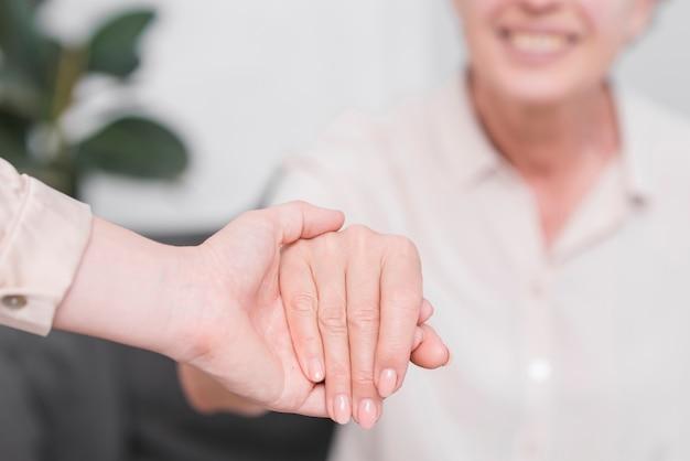 Primer plano de una mujer con mano de mujer senior Foto gratis