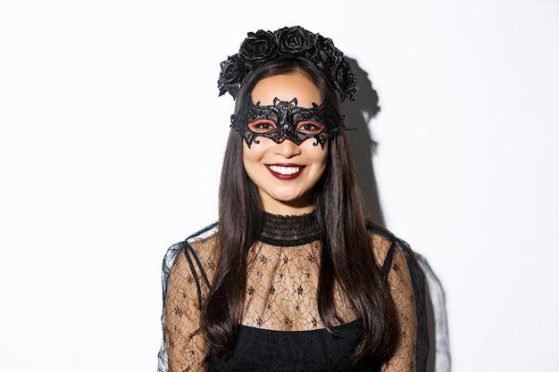 Primer plano de mujer misteriosa en corona gótica y máscara negra, celebrando halloween, de pie sobre una pared blanca Foto gratis