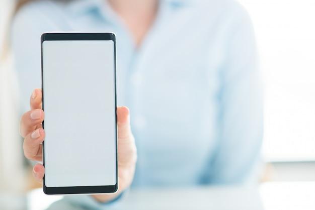 Primer plano de mujer mostrando la pantalla vacía del teléfono inteligente Foto gratis