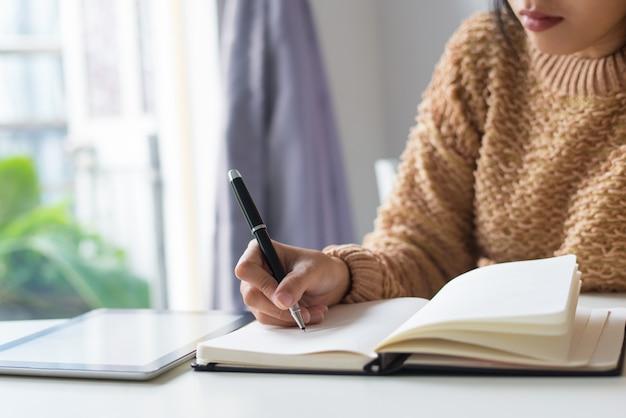Primer plano de la mujer pensativa escribir ideas en el diario Foto gratis