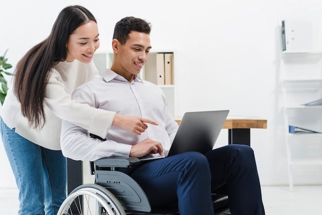 Primer plano de una mujer de pie detrás del empresario sentado en silla de ruedas mostrando algo en la computadora portátil Foto gratis