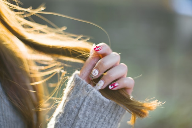Primer plano de mujer con las uñas pintadas tocando su pelo Foto gratis