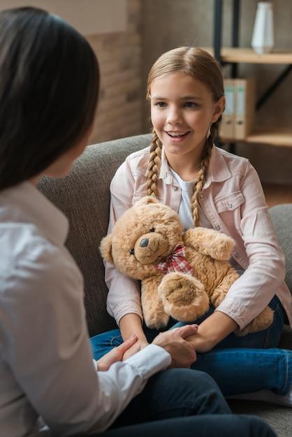 Primer plano de mujer psicóloga tomados de la mano de su paciente con osito de peluche Foto Premium