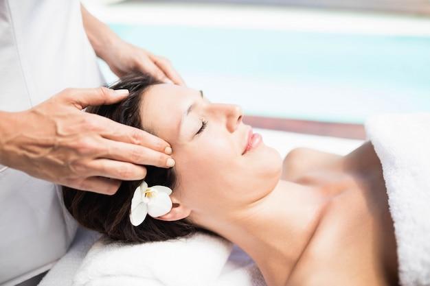 Primer plano de mujer que recibe un masaje de cabeza de masajista en un spa Foto Premium