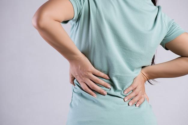 Primer plano de mujer que tiene dolor en la espalda lesionada Foto Premium