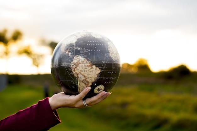 Primer plano de una mujer sosteniendo un globo terráqueo Foto gratis