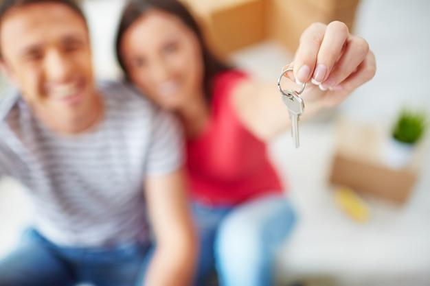 Primer plano de una mujer sosteniendo una llave Foto gratis