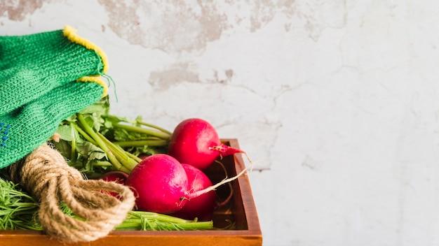 Primer plano de nabo rojo orgánico cosechado en bandeja de madera con fondo de hormigón Foto gratis