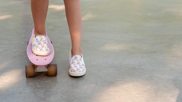 Primer plano de niña en patineta Foto gratis