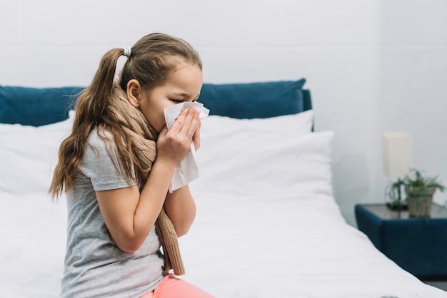 Primer plano de una niña que tiene frío soplando su nariz que moquea con tejido Foto gratis
