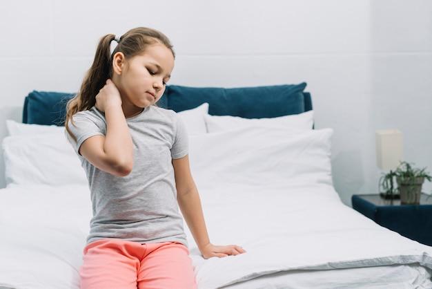 Primer plano de una niña sentada en la cama teniendo dolor en el cuello Foto gratis