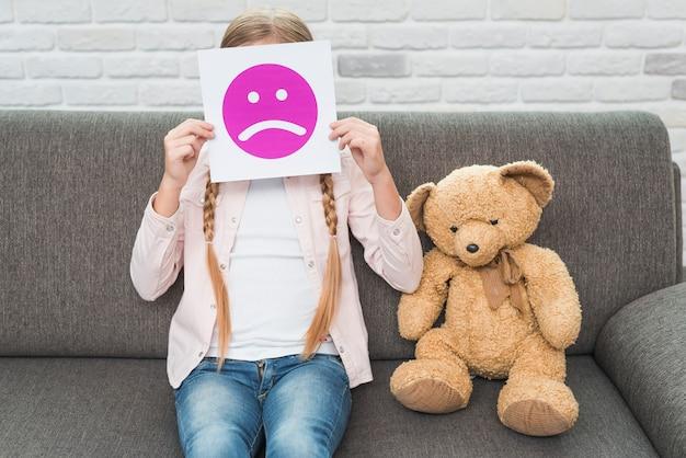 Primer plano de una niña sentada con peluche sosteniendo papel de emoticonos de cara triste frente a su cara Foto gratis