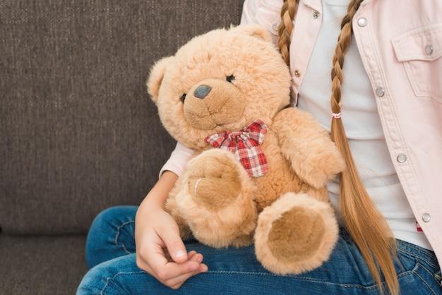 Primer plano de una niña sentada en el sofá con suaves osos de peluche Foto Premium