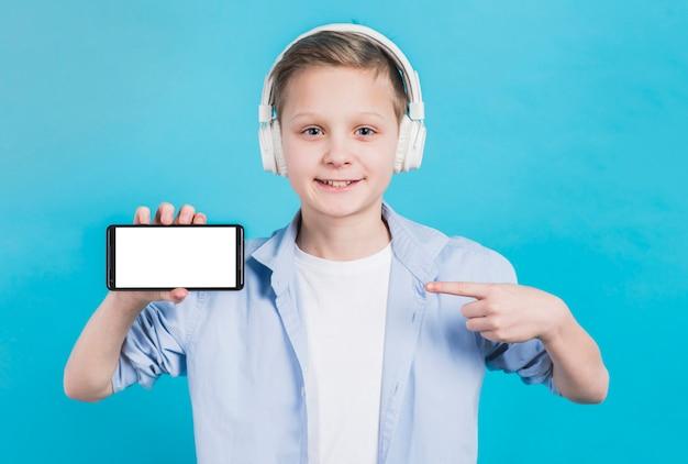 Primer plano de un niño con auriculares en la cabeza apuntando su dedo hacia el teléfono móvil con pantalla en blanco Foto gratis